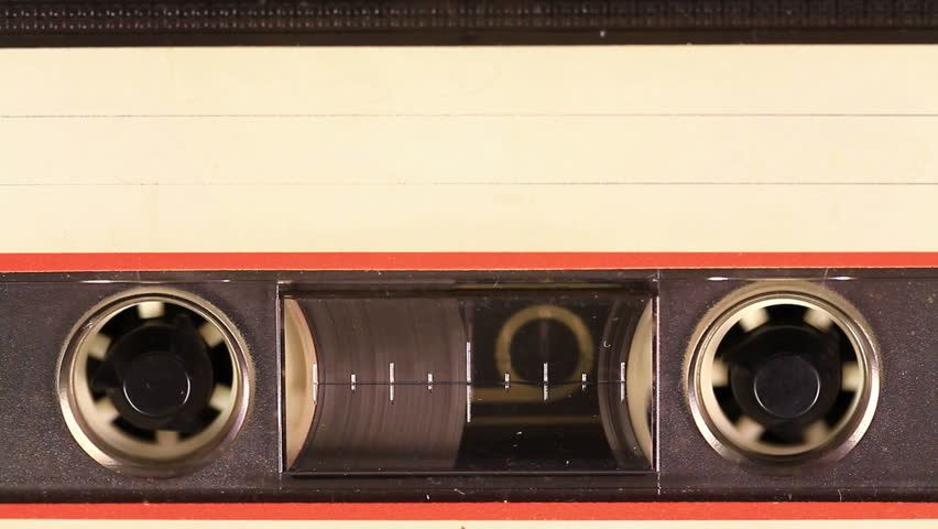 Macro static camera view of vintage audio cassette tape with a blank white label in use sound recording in a cassette player. Cassette Tape with a white blank label