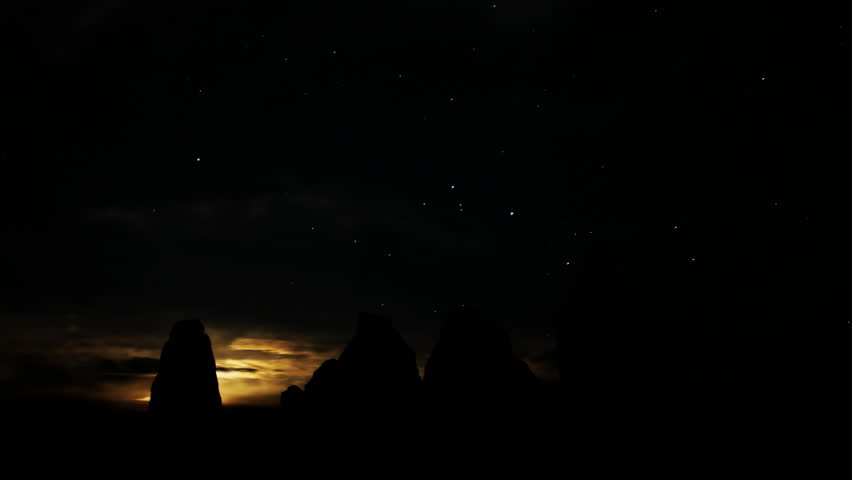 Astrophotography time lapse footage with zoom in motion of moon rising over monolithic formation in the desert of Trona, California