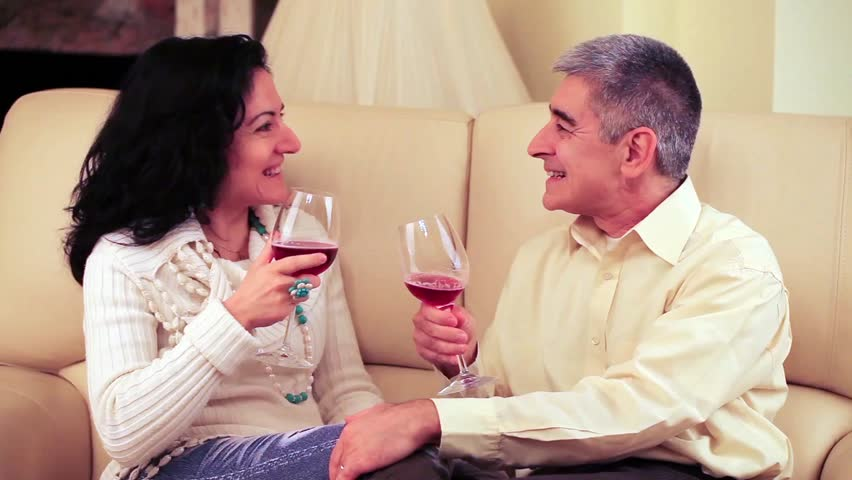 Video of a happy loving mature couple drinking a glass of red wine, joking and laughing on the sofa of their living room.