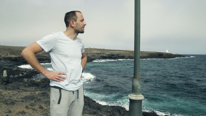 Handsome male jogger resting standing on rocks by sea, slow motion shot at 240fps  | Shutterstock HD Video #8706739