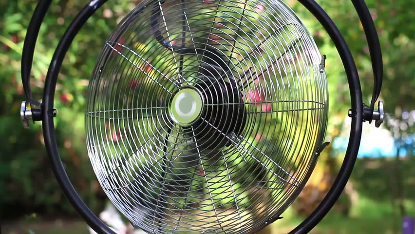 Fan making wind at camp place on a hot summer day in the forest. Close up shot of working moving big, old vintage fan spinning.