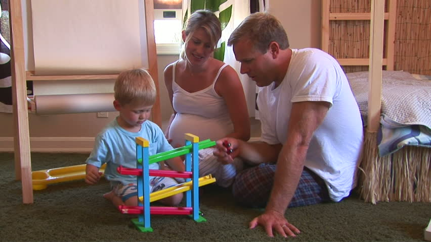 father and pregnant mother playing with toddler son in