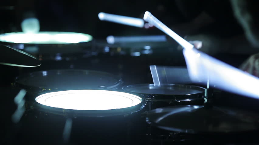 Playing glowing drums with neon drumsticks. Close-up