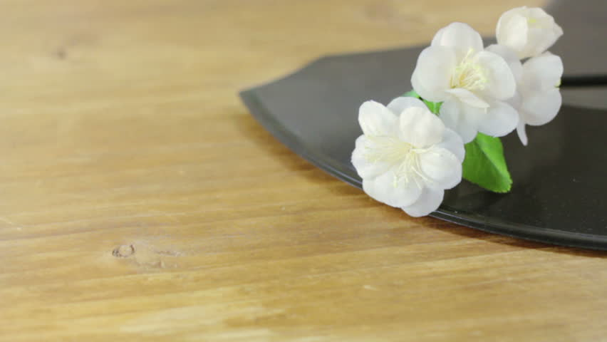 Artificial jasmine flowers on a broken gramophone record. Image on a wooden background.