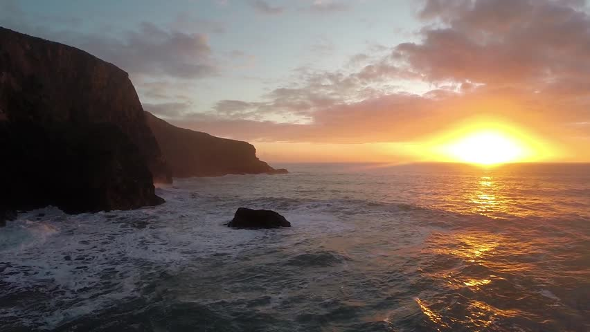 Flying over a huge boulder as a wave crashes over it at sunset and a seagull crosses the scene (Cornwall, UK) [50% speed]. Preceded by long, seamless approach across the bay, available separately.
