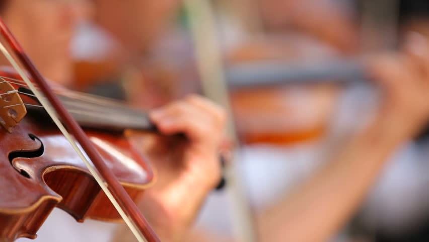 Violinists in the orchestra. Several violinists played professional tone. The background is blurred. - HD stock video clip