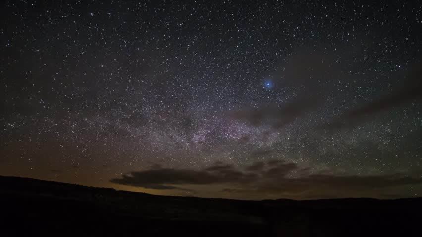 Time lapse of milky way rising above horizon with clouds moving in and out on a dark night in eastern Washington State