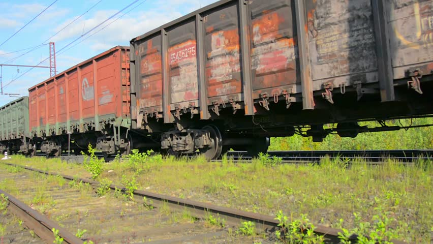 POLJARNIE ZORI. RUSSIA - CIRCA JUN 2014: Long freight train rolling by a rural area on its way to an unknown destination - HD stock footage clip