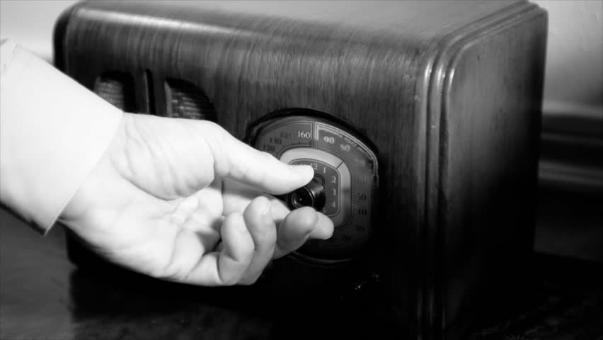 A man's hand turns the dial on an old vintage 1940's radio until he finds the music he is looking for, stops and starts tapping his finger. Film Noir