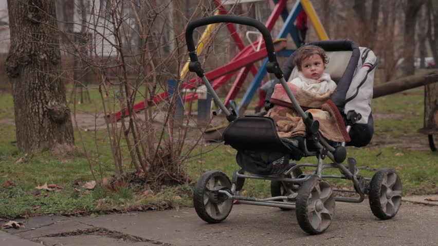 Baby in stroller. Kid waiting for parents in the park. Mother collecting branches for heating. Father pushing the transport trolley with firewood. Children playing on the swing. Poor gypsy family. | Shutterstock HD Video #8845015