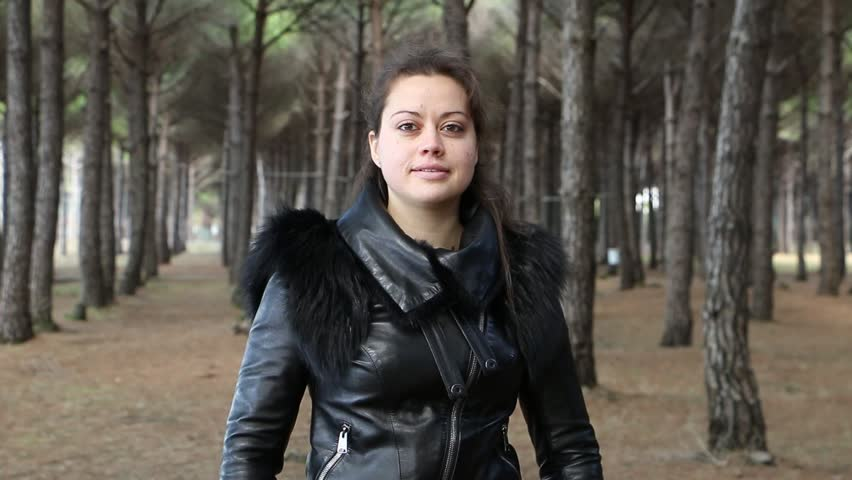 A young woman in a black leather jacket is spinning around in a pine forest. - HD stock video clip