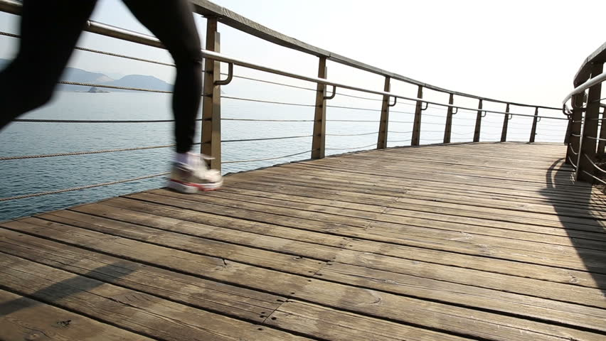 young sports woman running on seaside wooden boardwalk - HD stock footage clip