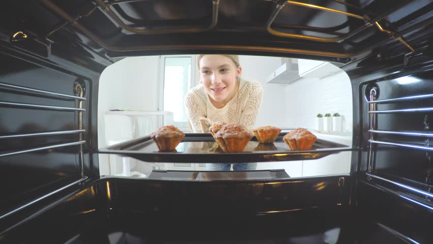 Cooking at home, Baking in the oven. Beautiful girl in her kitchen puts her cake into the oven 4K
