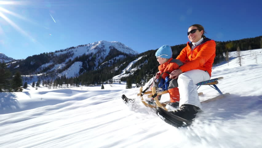 mother and son having fun sledging on snow