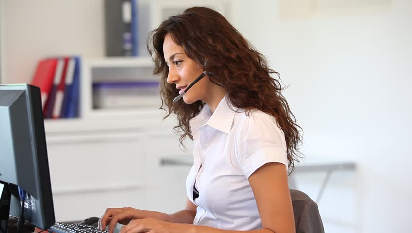 Woman in the office with headset on - HD stock video clip