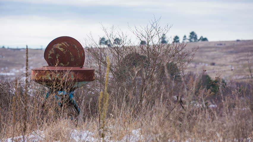 Empty landscape with rusty old farm device. Old farm equipment in tall field grass in bad weather abandoned in wind. - HD stock video clip
