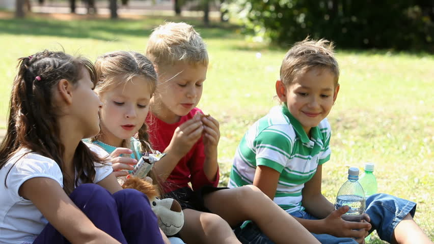 Five children sitting on grass in the park and eating, one girl drinking mineral water  - HD stock video clip