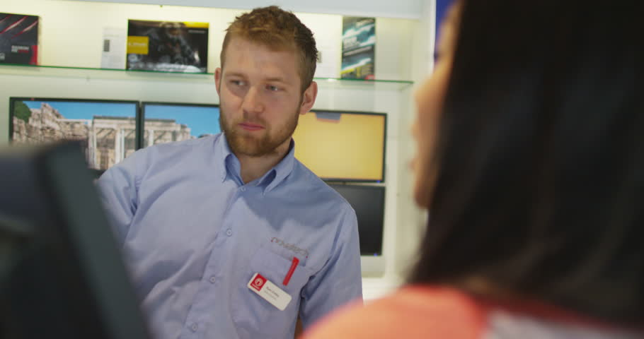 4K Salesman taking payment from customer in consumer electronics store showroom