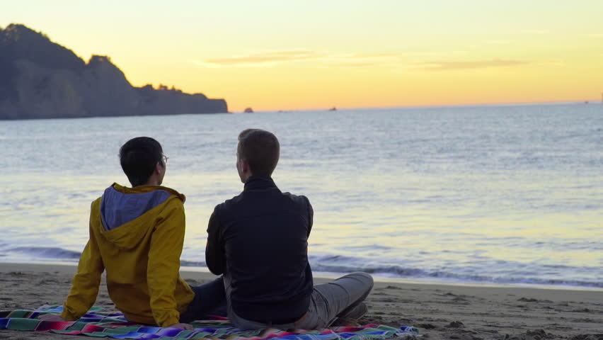 Gay Couple Sit On Blanket And Watch The Sunset At The Beach