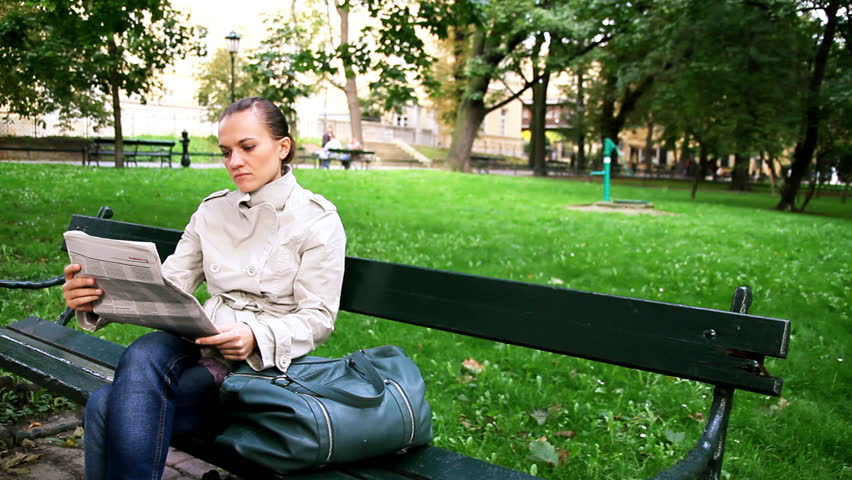 Woman sitting in the park and reading newspaper, dolly shot  - HD stock footage clip