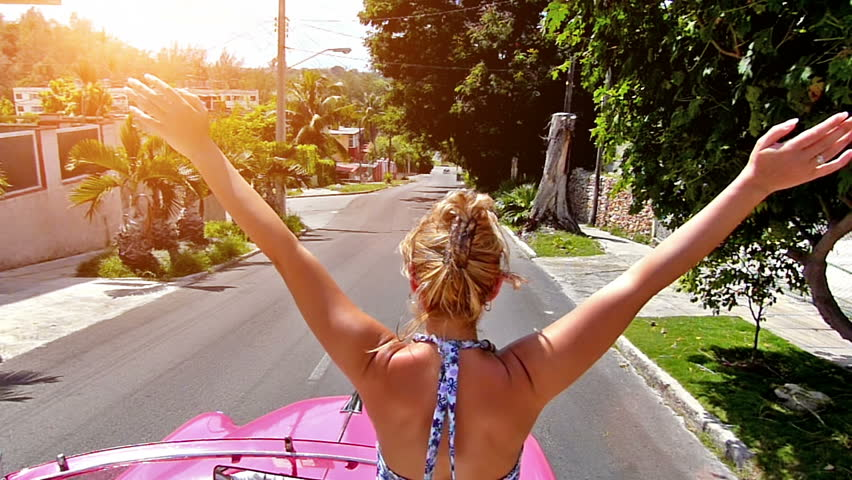 Rear view of happy blonde woman with arms outstretched, driving in pink cabriolet through Havana city, Cuba.Slow motion, high speed camera, lens flare - HD stock footage clip