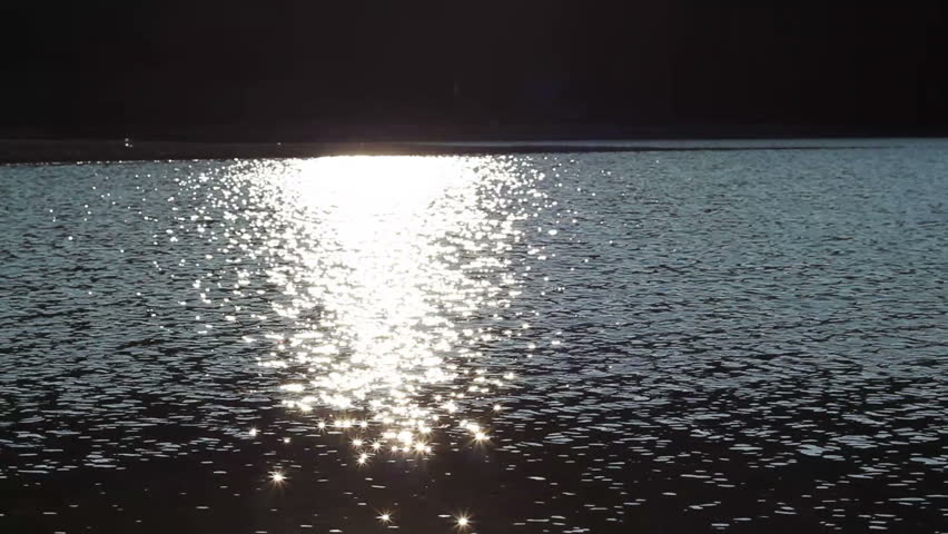 Afternoon sun is reflecting in the lake water and produce thousands of dazzling stars flashes. - HD stock video clip