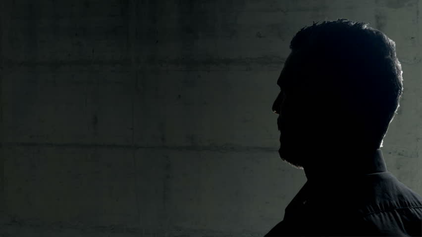witness  anonymous man being interviewed in a dark room  silhouette lateral view 4k