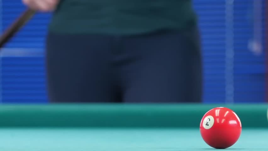 Young smiling blond woman in green svitshote playing billiards. Slow motion