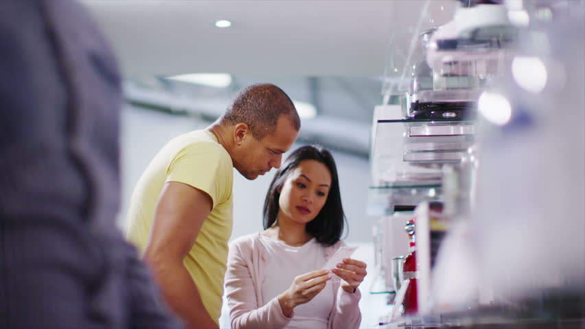 4K Couple shopping in a store selling kitchen appliances, white goods & electronics