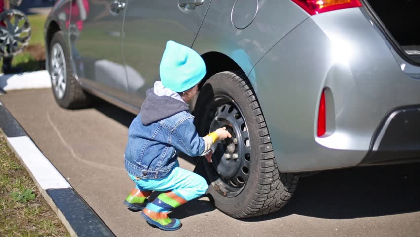Little girl and boy tie rear wheel of car with socket wrench.  - HD stock video clip