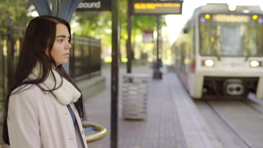 Mixed Race Young Woman Waits For A Train On A Beautiful Day In The City