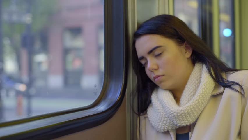 Mixed Race Teen Girl Sleeps On The Train On A Sunny Day In The City