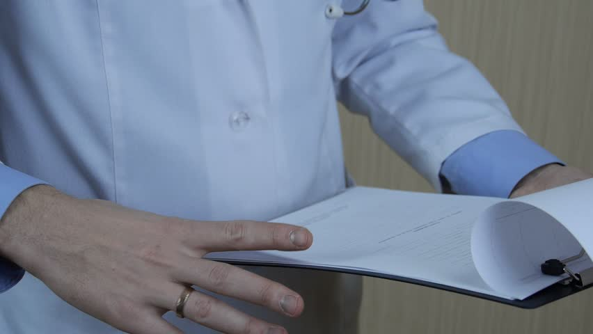 Doctor examine, review forms with the testimony of evaluable patients. The patient is healthy, the doctor carefully examines evidence analysis. - HD stock footage clip