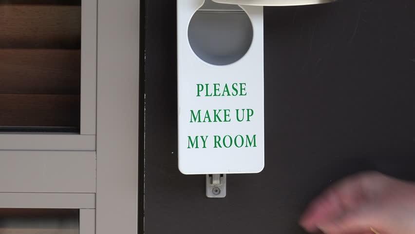 Woman hangs please make up my room sign on hotel or motel door