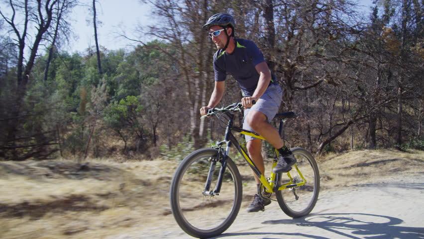 Man riding mountain bike down gravel road, tracking shot