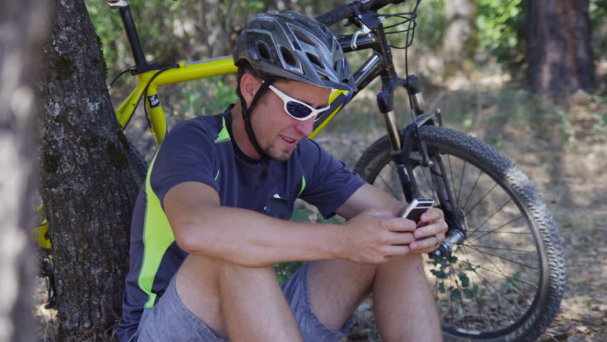Man with mountain bike sits down taking break and checking cell phone