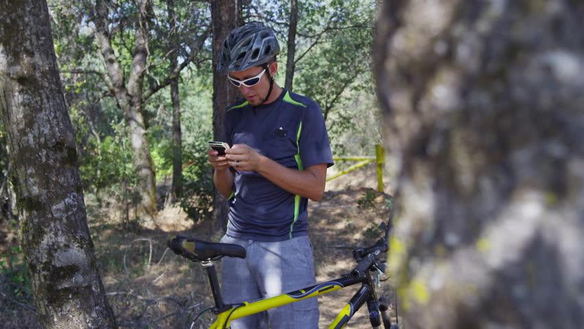 Mountain biker takes a break to check cell phone