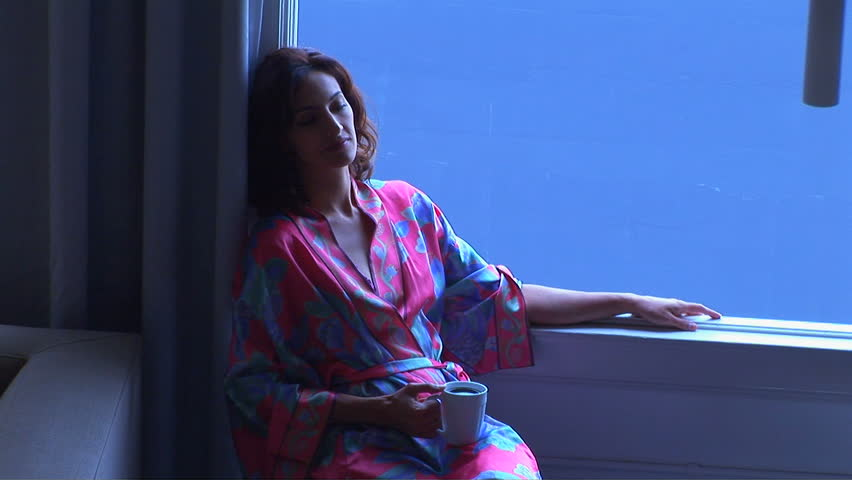 Young woman sitting with coffee looking out window - HD stock footage clip
