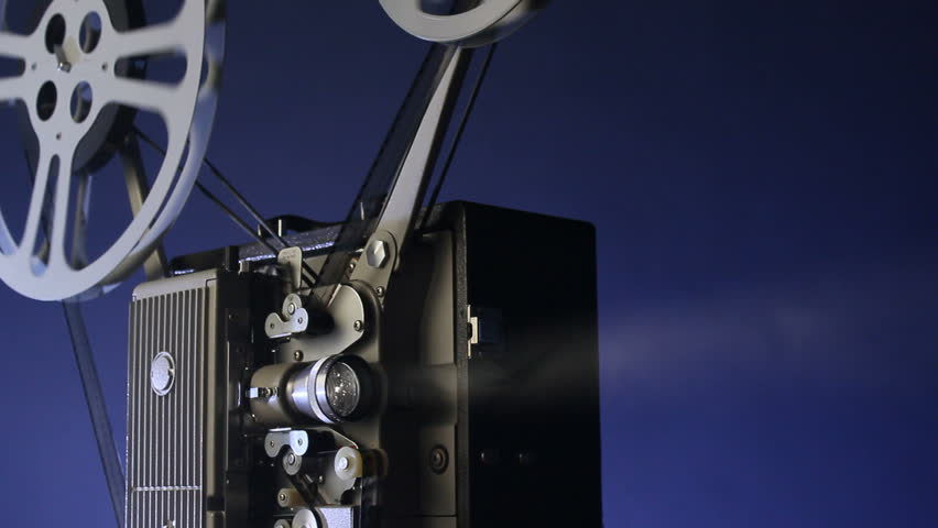 A motion picture movie projector sends a beam of light into the dark
