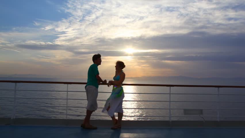 couple having joined hands stands on ship moving in sea during sunset - HD stock footage clip
