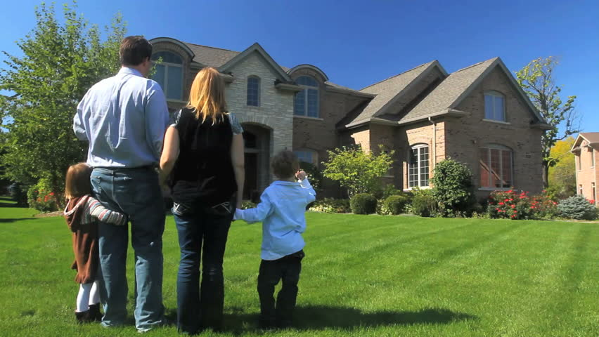 A family stands together in their yard, facing their luxury home  | Shutterstock HD Video #921532
