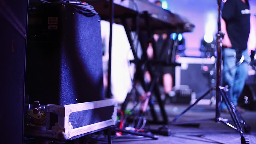 Shot of a stage during setup before a show. Stage hands can be seen setting up equipment and also instruments such as Guitar amps and Keyboard stands on the shot.
