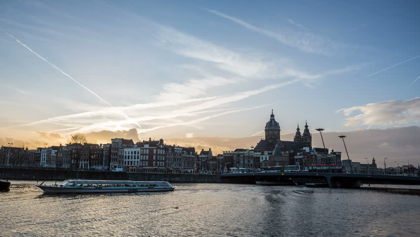 AMSTERDAM, NETHERLANDS – February 8, 2015: Sunset with cloudy Sky and town near main station with city life - DSLR timelapse