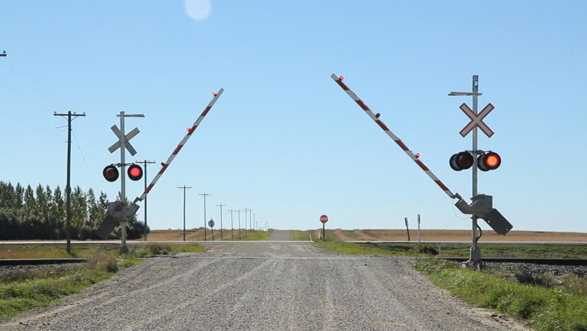 Rail crossing with sound of train coming. Gates lowering.