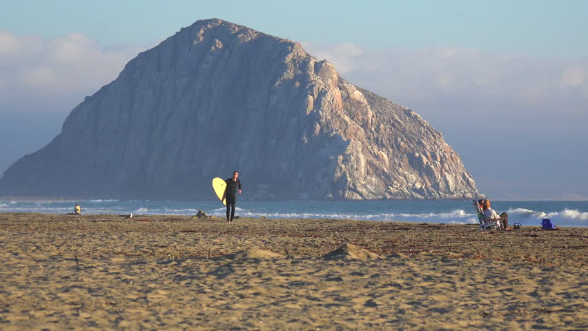 MORRO BAY, CALIFORNIA - CIRCA 2014 - A surfer crosses in front of the beautiful Morro Bay rock along California's central coast. - 4K stock video clip