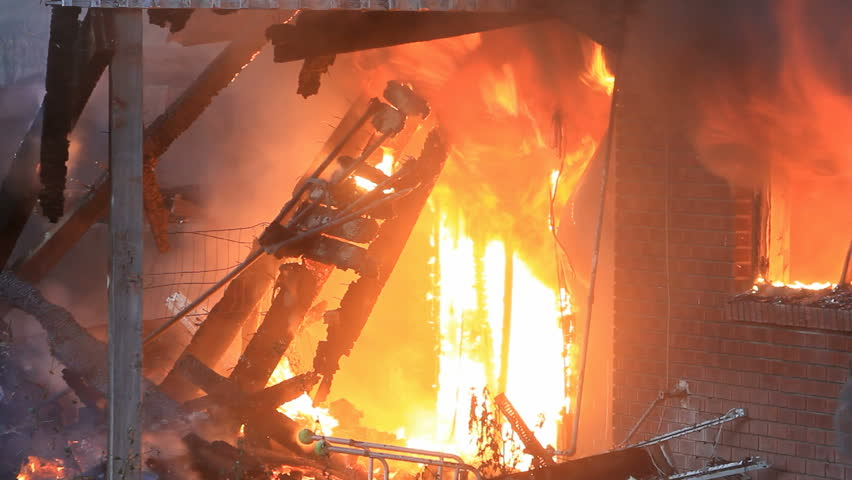 House destroyed by intense fire. Flames engulfing the interior of a home