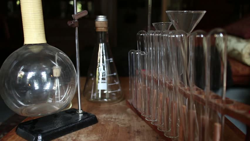 DOLLY MOVE INTO TEST TUBES & BEAKERS (One of Series) POV - CURRENT SHOT: Macro dolly moves out from and into an arrangement of vintage beakers and test tubes; shallow DOF blurs out noticeable marks. - HD stock footage clip