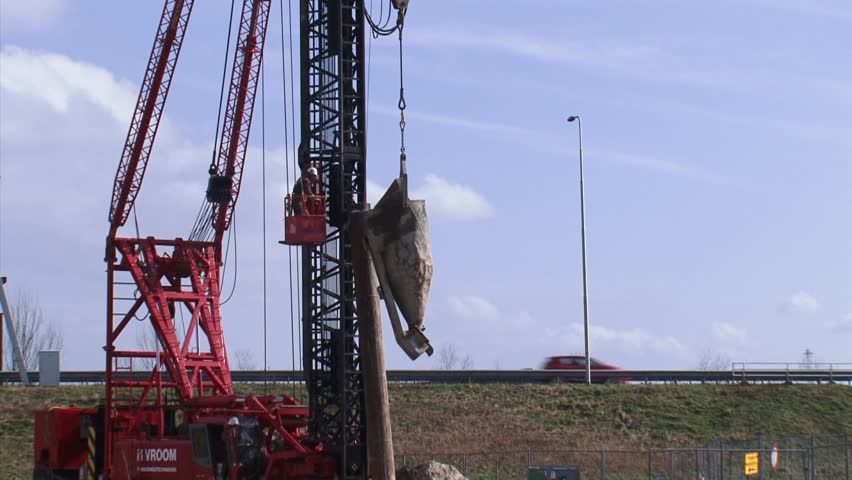 THE NETHERLANDS - 10 MARCH 2015: Construction site along highway A12/A30, worker hoisting a concrete box for cast-in-situ application, pour the concrete at the pipe connection