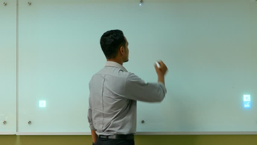 """A male worker write """"Our mission"""" on the interactive board while presenting."""