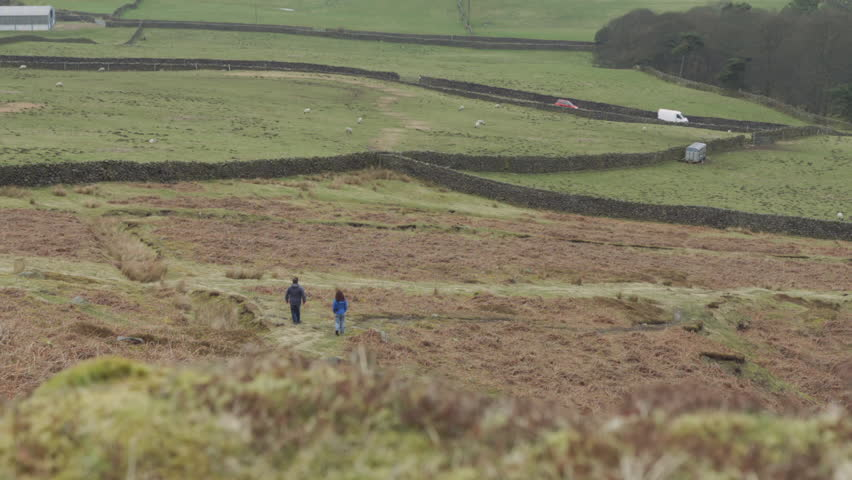 Two people waling on the Moor. Two people exploring the beautiful Yorkshire moor and farmlands with Sheep in the background. Filmed on the BMD Cinema Camera. ProRes 422.